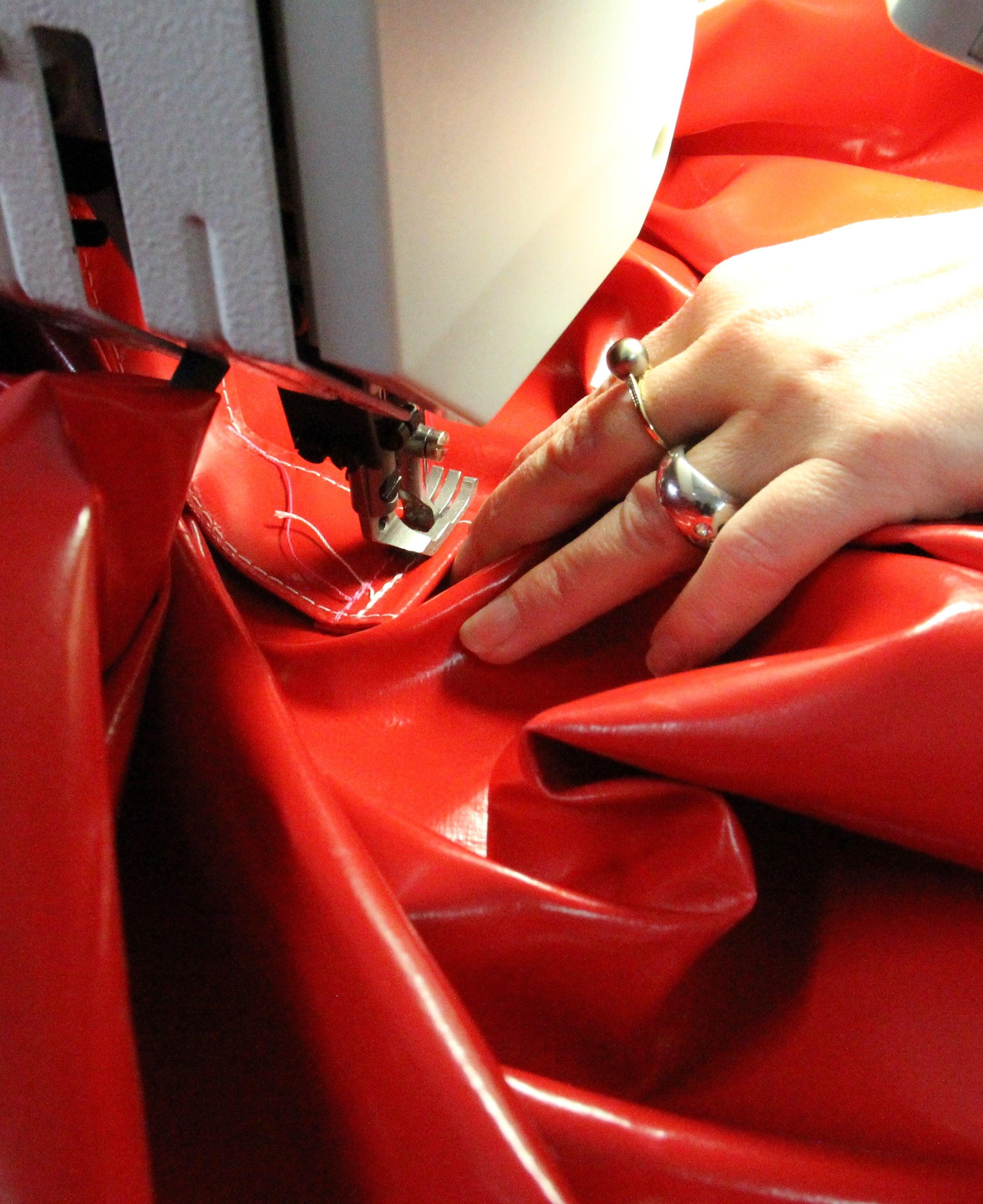 Main d'une couturière d'une housse de protection